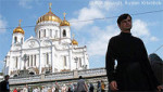 File Photo of Russian Orthodox Cathedral with Man in Religious Garb in Foreground