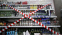 Shelf of Alcoholic Beverages with Red and White Tape Across It
