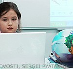 File Photo of Little Girl at Computer Next to Globe
