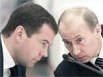 File Photo of Dmitry Medvedev and Vladimir Putin with Heads Bowed Over Microphone