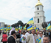 File Photo of Ukrainians with Ukrainian Flag in Public Square Near Tower with Golden Dome