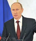 File Photo of Vladimir Putin Speaking with Flag Behind Him and Microphones in Front