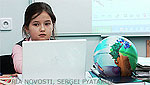 File Photo of Little Russian Girl at Laptop Next to Globe