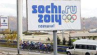 File Photo of Sochi Olympics Banner Near Highway in Warm Weather with Vehicle and Cyclicsts Nearby