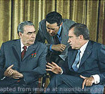 File Photo of Richard Nixon sitting with Leonid Brezhnev, with Third Person Standing and Leaning between Them