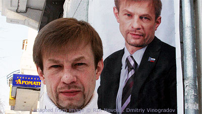 File Photo of Yevgeney Urlashov Standing Near One of His Campaign Posters
