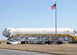 Antares Rocket on Side on Transport Vehicle As U.S. Flag Flies on Pole