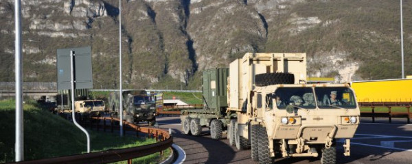 U.S. Military Convoy Headed to Ukraine, On Highway Near Mountains or Cliffs