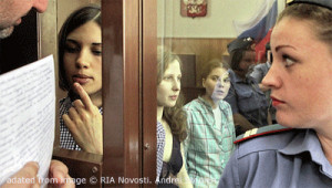 File Photo of Pussy Riot Members in Courtroom Enclosure, With Man Showing Papers to One While Female Guard Looks On
