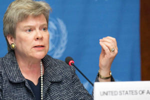 File Photo of Rose Gottemoeller Gesturing, Sitting Behind Placard Reading United States of America
