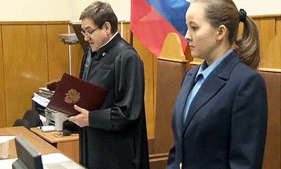 File Photo of Judge and Clerk in Russian Court, with Russian Flag Behind Bench