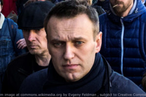 File Photo of Alexei Navalny Marching on Street with Others in Background; adapted from image at commons.wikimedia.org by Evgeny Feldman, subject to Creative Commons license; original image at https://commons.wikimedia.org/wiki/File:FEV_1795_(cropped1).jpg, with license information at https://creativecommons.org/licenses/by-sa/4.0/deed.en and https://creativecommons.org/licenses/by-sa/4.0/legalcode