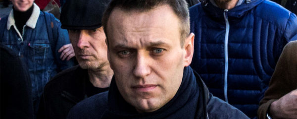 File Photo of Alexei Navalny Marching on Street with Others in Background; adapted from image at commons.wikimedia.orgadapted from image at commons.wikimedia.org with credit to Evgeny Feldman, subject to Creative Commons license; original image at commons.wikimedia.org/wiki/File:FEV_1795_(cropped1).jpg, with license information at creativecommons.org/licenses/by-sa/4.0/deed.en and creativecommons.org/licenses/by-sa/4.0/legalcode