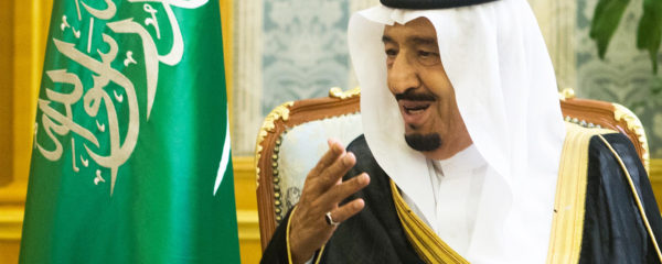 File Photo of King Salman of Saudi Arabia Seated Next to Saudi Flag and Gesturing, adapted from image at defense.gov