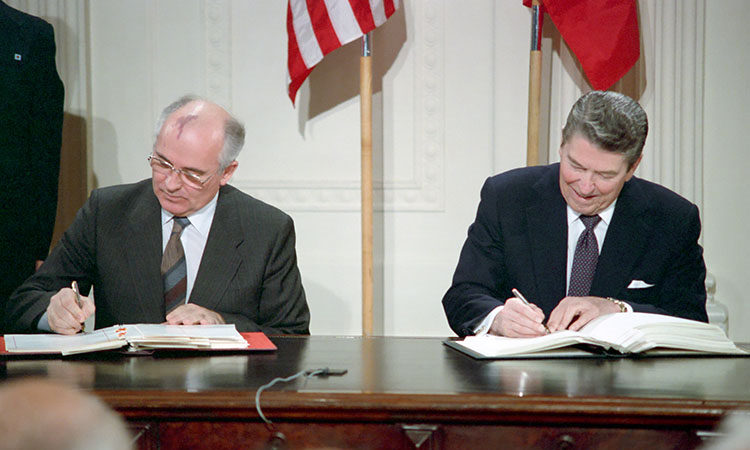 File Photo of Mikhail Gorbachev and Ronald Reagan at Table Signing Documents