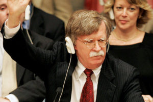 File Photo of John Bolton Raising Hand at United Nations, with United States Nameplate on Desktop in Front, adapted from image at state.gov