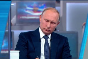 File Photo of Putin Sitting at Desk, Looking Down, Writing, During Call-In Show, adapted from screenshot of video at kremlin.ru