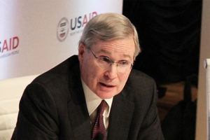 File Photo of Stephen Hadley At Table Leaning Forward, with USAID Logo Partially Obscured in Background, adapted from image at usaid.gov by Steven C. Welsh :: www.stevencwelsh.com :: www.stevencwelsh.info