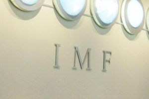 File Photo of IMF Acronym on Wall Below Row of Circular Lights, adapted from image at state.gov by Steven C. Welsh :: www.stevencwelsh.com :: www.stevencwelsh.info