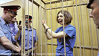 File Photo of Pussy Riot Member in Courtroom Cage, Grinning and Gesturing with Clasped Hands