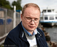 File Photo of Oleg Kashin Outdoors with Boat and Water in Background