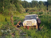 File Photo of People Working on Car Amidst Siberian Woodlands and Meadows