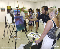 File Photo of Artists in Vladivostok Studio with Paintings on Easels, with American Artist Demonstrating Technique to Russians