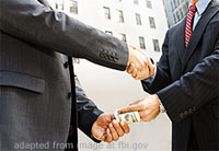 Cropped File Photo of Two Men in Business Suits Shaking Hands and Passing Cash