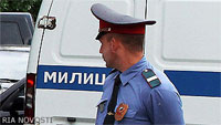 File Photo of Russian Policeman with Face Turned Towards Van