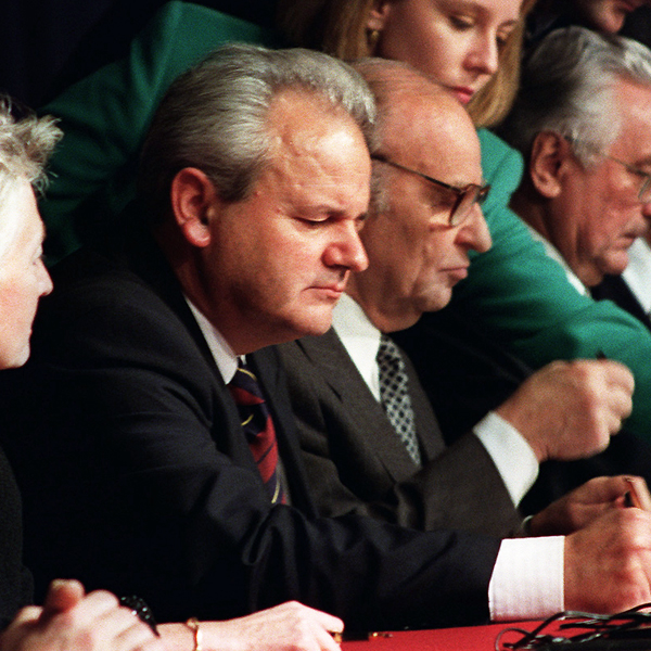 File Photo of Slobodan Milosevic at Table in Profile, Surrounded by Officials and Others
