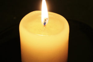 Lit Candle with Reflection and Dark Background
