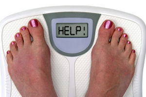 File Photo of Feet of Woman on Scale, With Red Toenails and Help on Scale Digital Display Screen