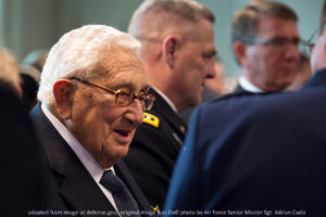 Henry Kissinger File Photo, with Military Officer and Others in Background; adapted from image at defense.gov,; original image was DoD photo by Air Force Senior Master Sgt. Adrian Cadiz