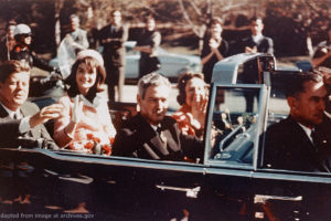 John F. Kennedy, Jacqueline Kennedy and Other Parties in Open-Air Limousine On Street Just Before Assassination, With Crowd in Background, adapted from image at archives.gov