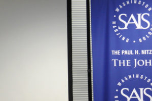 File Photo of Banner with SAIS Logos in Washington, D.C., Near Gray Wall, adapted from image at ustr.gov