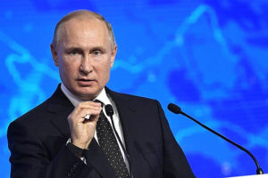 File Photo of Vladimir Putin at Podium with United Russia Logo, Gesturing