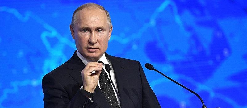 File Photo of Vladimir Putin at Podium with United Russia Logo, Gesturing