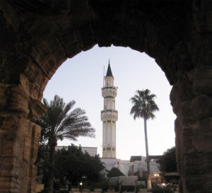 File Photo of Ancient Roman Arch in Libya Framing Minaret and Palm Trees, adapted from image at cia.gov