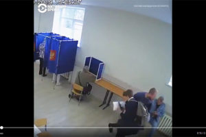Screenshot of Video at https://twitter.com/CurrentTimeTv/status/1171888101989539842 showing man punching another man in the stomach at Russian polling place while second man was looking down at mobile device