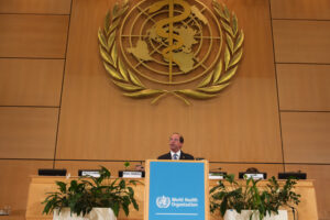 File Photo of World Health Assembly at WHO, with Alex M. Azar II at the Podium, adapted from image featured at geneva.usmission.gov
