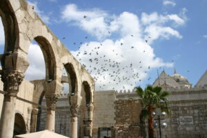 File Photo of Historic Buildings and Archway in Syria with Birds Taking Flight in Background, adapted from image at state.gov