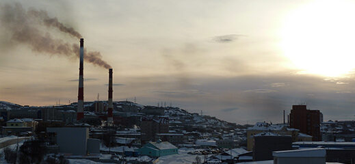 File Photo of Smokestacks Spewing Pollution in Murmansk, Russia, at twilight or before dawn, adapted from image at pnnl.gov with photo credit to N. Kholod